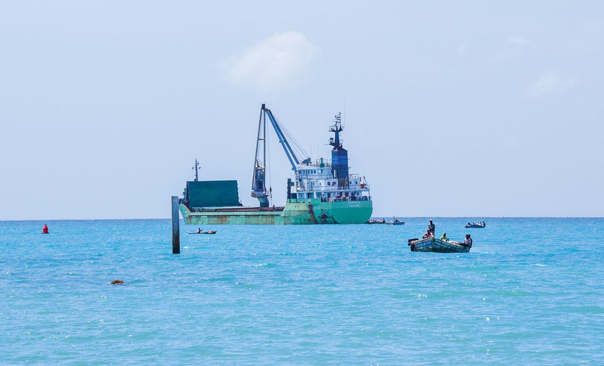 UN BATEAU au large du quai des Cayes débarque sa cargaison de ciment à l'aide de canots