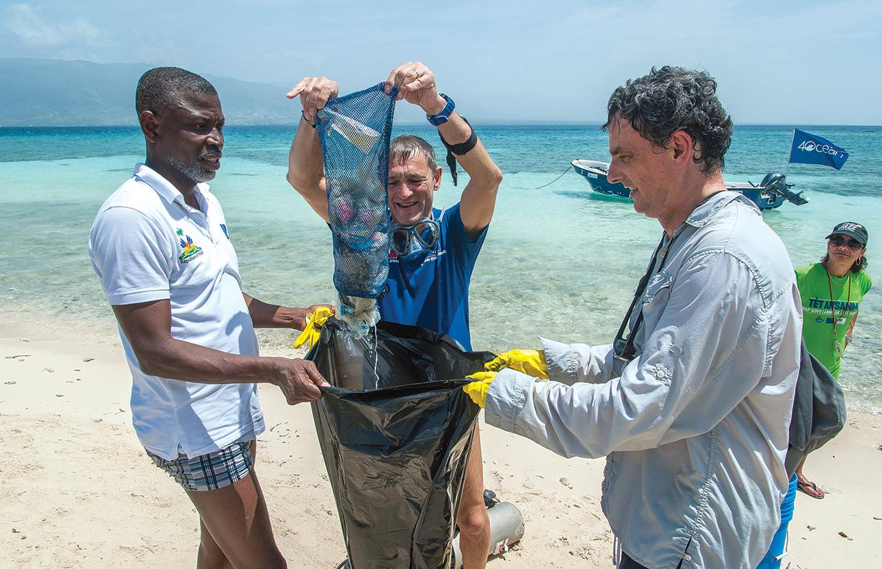 L'ambassadeur Vincent Degert déverse ses «prises» dans le sac que lui tendent Hervé Philippe, le représentant du BUreau de l'Ordonnateur National ( à gauche) et l'ambassadeur d'Espagne en Haïti, Pedro Sanz ( à droite).